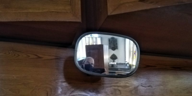 Maskiertes Gesicht im Orgel-Spiegel